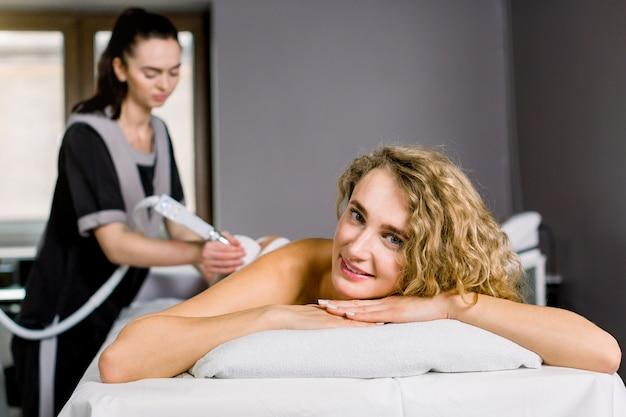 Mulher loira bonita sorrindo, olhando para a câmera enquanto estiver recebendo tratamento de cavitação por ultra-som por cosmetologista.