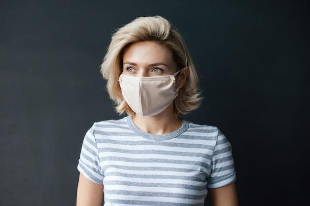 Mulher loira branca olhando para algum lugar, posando na parede cinza de um estúdio com uma máscara médica no rosto