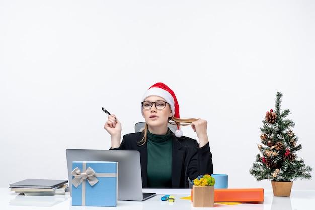 Mulher loira brincando com um chapéu de papai noel, sentada à mesa com uma árvore de natal e um presente