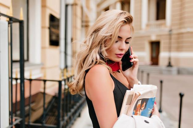 Mulher loira calma ligando para um amigo e indo para casa com jornal novo