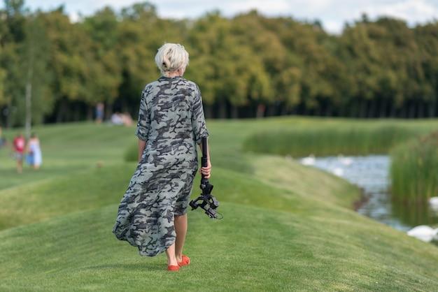 Mulher loira caminhando ao lado de um lago carregando um tripé e uma câmera enquanto o vento sopra o tecido de seu vestido longo para o lado