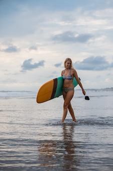 Mulher loira caminhando na praia com sua prancha de surfe