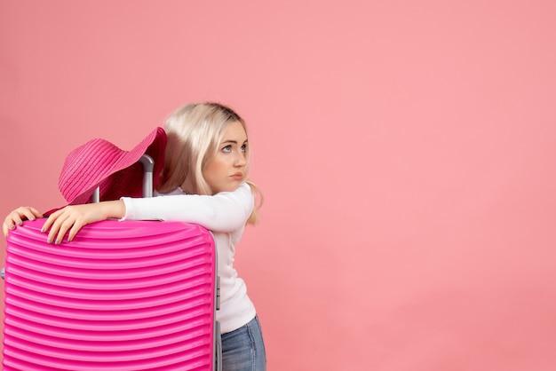 Mulher loira cansada de frente segurando a mala com chapéu-panamá