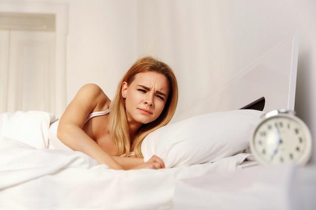 Mulher loira cansada odia o relógio enquanto ela acorda