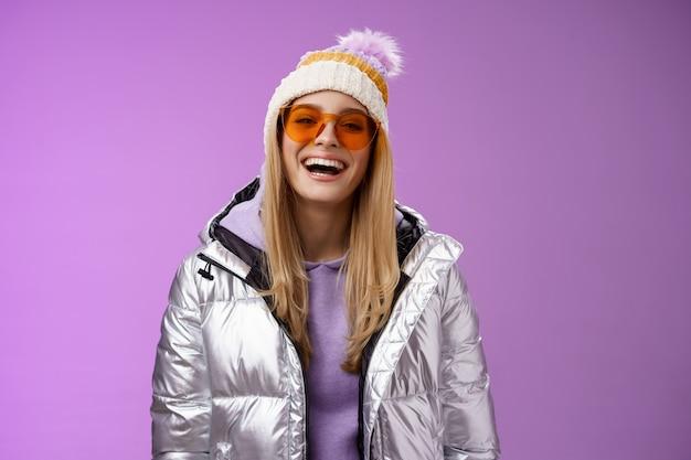 Mulher loira carismática amigável elegante em óculos de sol de chapéu de jaqueta brilhante prata pronto aprender snowboard sorrindo rindo alegremente se divertindo recreação na neve resort, fundo roxo de pé.