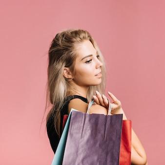 Mulher loira, carregando sacolas de compras