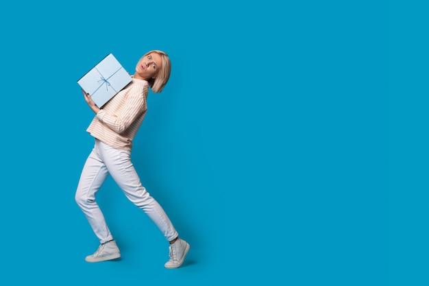 Mulher loira carregando uma caixa com um presente em um estúdio de parede azul anunciando algo