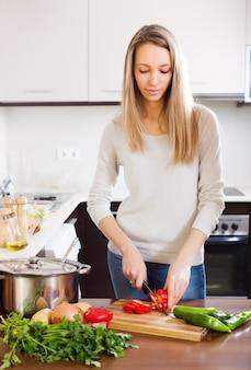 Mulher loira casual que corta a pimenta vermelha