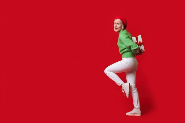 Mulher loira caucasiana carregando uma caixa de presente nas costas, usando um chapéu e olhando para a câmera em uma parede vermelha com espaço livre