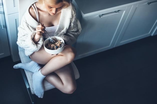 Mulher loira caucasiana com hábitos saudáveis comendo cereais no chão da cozinha vestindo um suéter de tricô