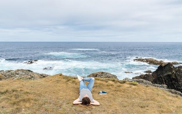 Mulher loira caucasiana deitada na grama relaxando à beira-mar