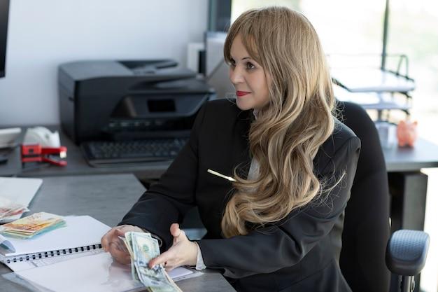 Mulher loira caucasiana elegante com cabelos ondulados compridos e brilhantes. contador sentado à mesa no escritório. retrato de mulher chocada e surpresa em um terno de negócio, contando notas de dólar, conceito de impostos