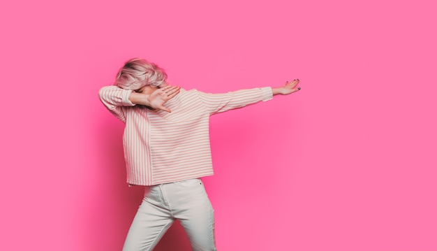 Mulher loira caucasiana enxugando a parede rosa de um estúdio com espaço vazio
