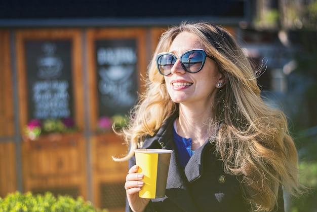Mulher loira caucasiana feliz bebendo café