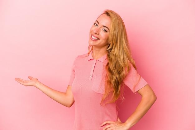 Mulher loira caucasiana isolada em um fundo rosa, mostrando uma expressão de boas-vindas.