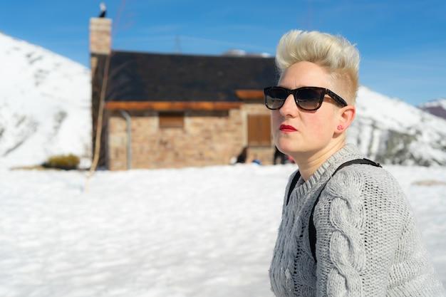 Mulher loira caucasiana na montanha coberta de neve no inverno