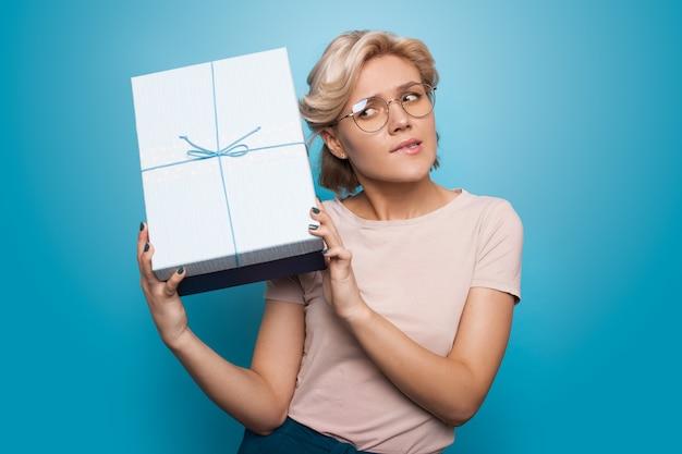 Mulher loira caucasiana ouvindo seu presente gesticulando impaciência na parede azul de um estúdio
