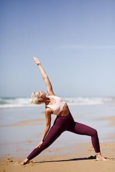 Mulher loira caucasiana praticando ioga na praia