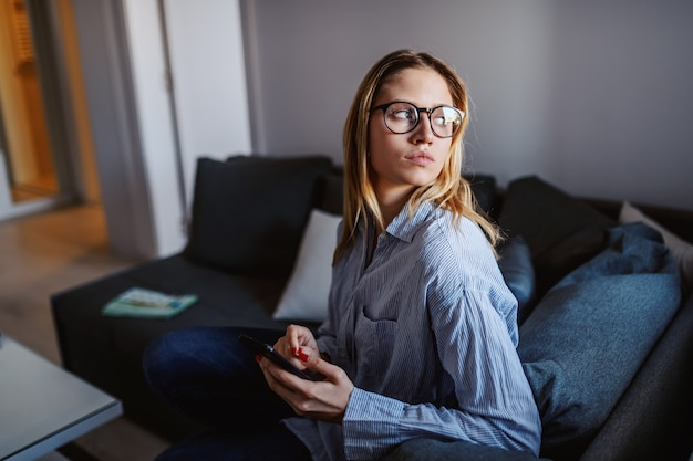 Mulher loira caucasiana séria jovem com óculos sentado no sofá na sala de estar, segurando o telefone inteligente e olhando pela janela da calha.