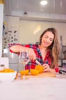 Mulher loira caucasiana tomando um suco de laranja fresco no café da manhã na cozinha, foto vertical