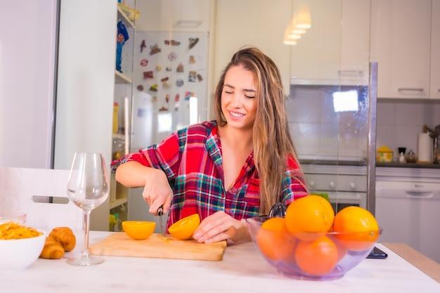 Mulher loira caucasiana tomando um suco de laranja fresco no café da manhã na cozinha