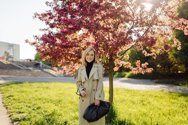 Mulher loira caucasiana vestindo trincheira sorrindo feliz em um dia ensolarado de primavera, caminhando no parque