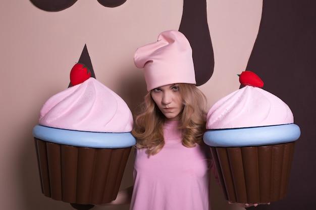 Mulher loira chateada com boné rosa segurando cupcakes grandes no estúdio