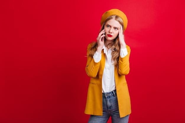 Mulher loira chateada com jaqueta amarela, falando no telefone. triste senhora caucasiana de boina em pé na parede vermelha com smartphone.
