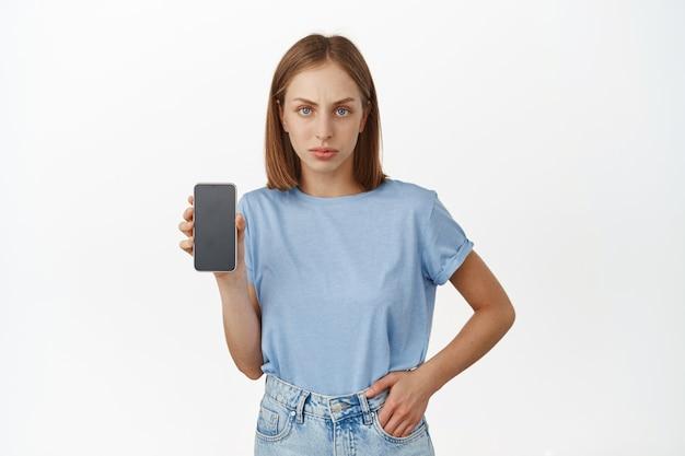 Mulher loira chateada, mostrando a tela do smartphone com expressão de rosto franzido e desapontada. mulher descontente reclama, mostra interface de celular, parede branca