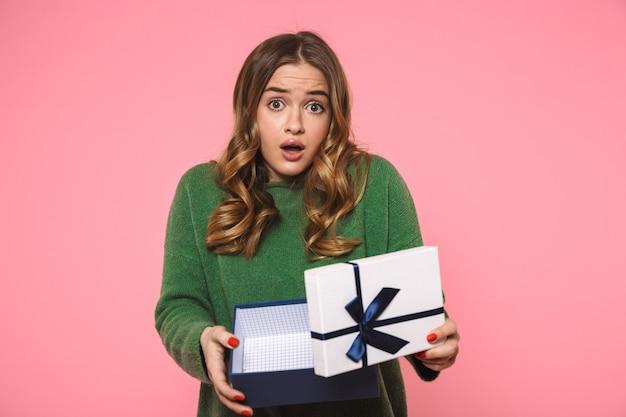 Mulher loira chocada usando um suéter verde abrindo uma caixa de presente e olhando para a frente sobre a parede rosa