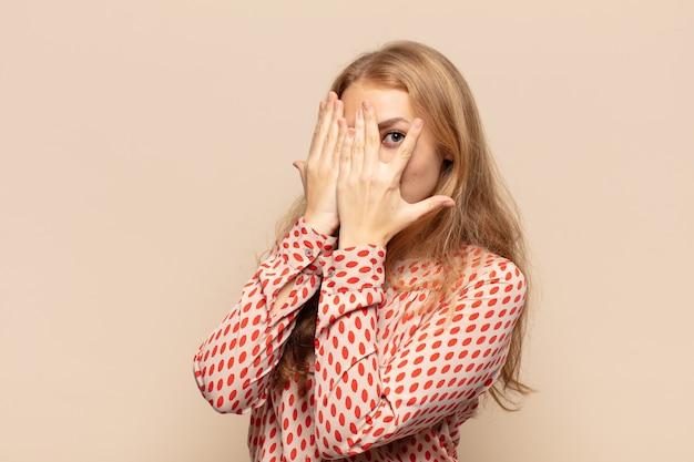 Mulher loira cobrindo o rosto com as mãos, espiando por entre os dedos com expressão de surpresa