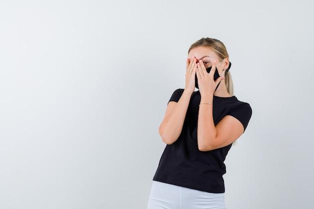 Mulher loira cobrindo o rosto com as mãos, olhando por entre os dedos em uma camiseta preta