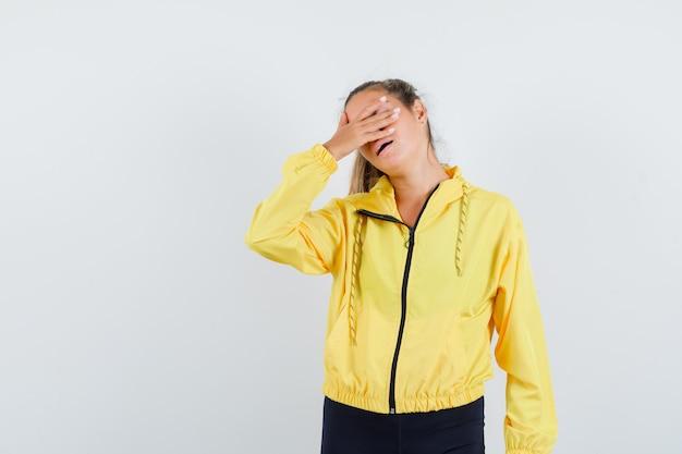 Mulher loira cobrindo os olhos com as mãos em uma jaqueta bomber amarela e calças pretas e parecendo preocupada