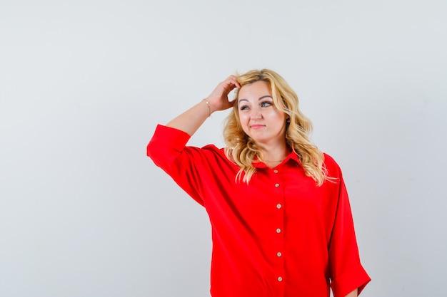 Mulher loira coçando a cabeça, pensando em algo com uma blusa vermelha e parecendo pensativa
