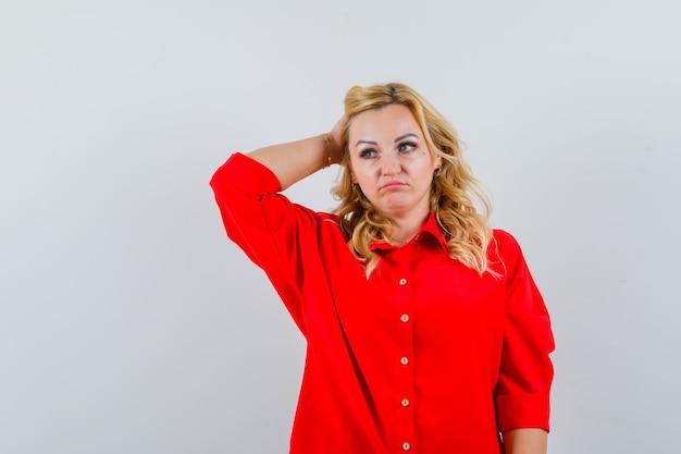 Mulher loira colocando a mão na cabeça, olhando para longe na blusa vermelha e parecendo pensativa.