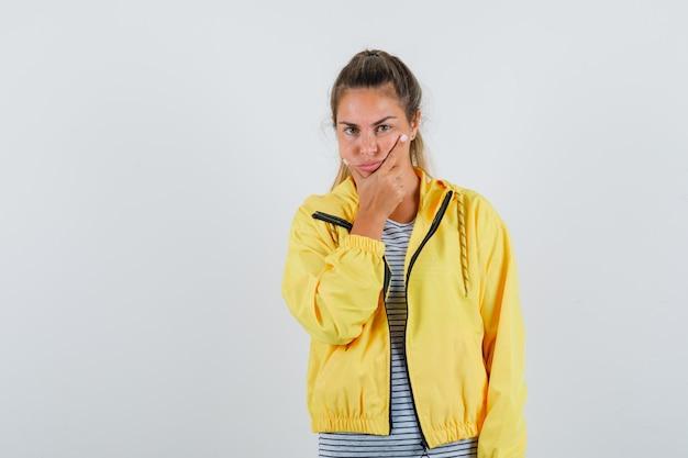 Mulher loira colocando a mão no queixo enquanto pensa em pose de jaqueta militar amarela e camisa listrada, parecendo pensativa
