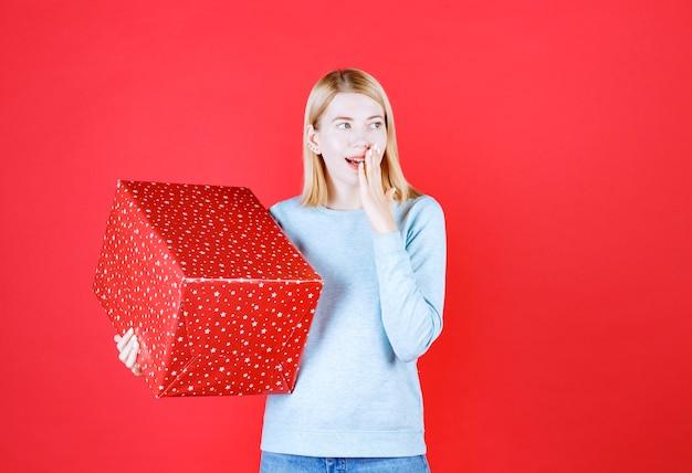 Mulher loira colocando a mão perto da boca enquanto segura a caixa vermelha e grande de presente
