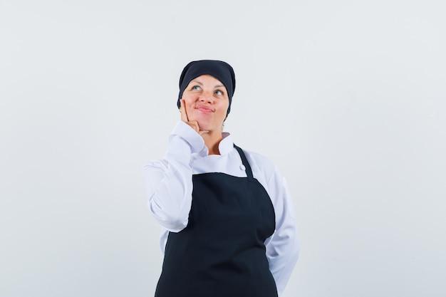 Mulher loira colocando o dedo indicador na bochecha, pensando em algo em um uniforme preto de cozinheira e bonita