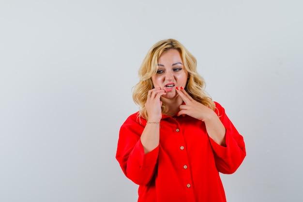 Mulher loira colocando os dedos no queixo, pensando em algo de blusa vermelha e parecendo pensativa,