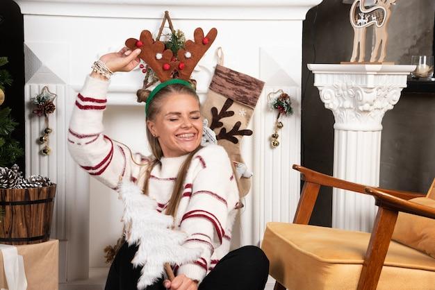 Mulher loira com árvore de natal branca felizmente sentada perto da lareira.