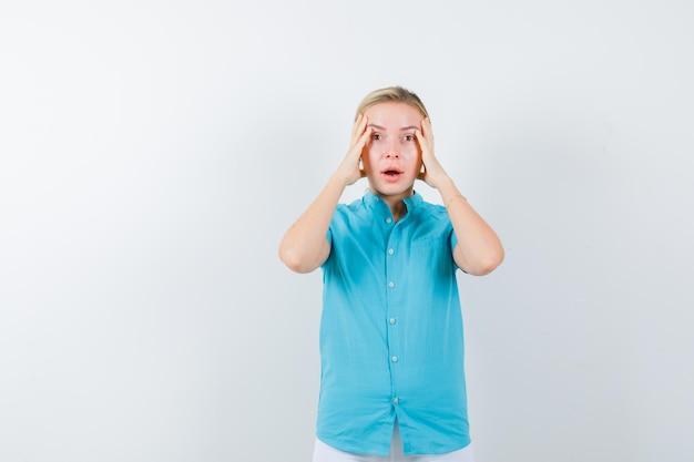 Mulher loira com as mãos na cabeça com blusa azul e parecendo desnorteada e isolada