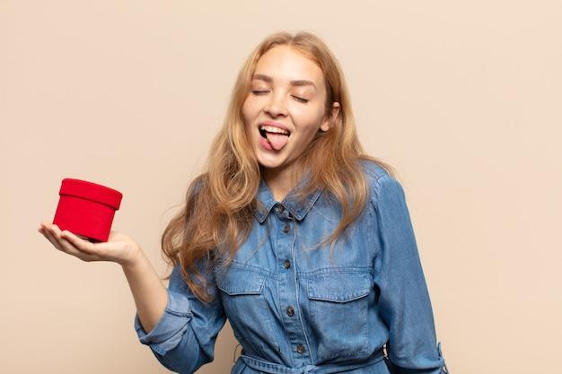 Mulher loira com atitude alegre, despreocupada, rebelde, brincando e mostrando a língua, se divertindo