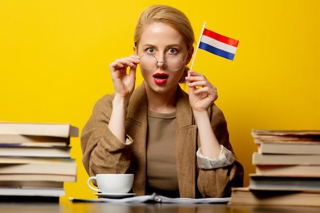 Mulher loira com bandeira da holanda e livros em amarelo