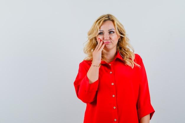 Mulher loira com blusa vermelha colocando a mão na bochecha, olhando para longe e pensativa