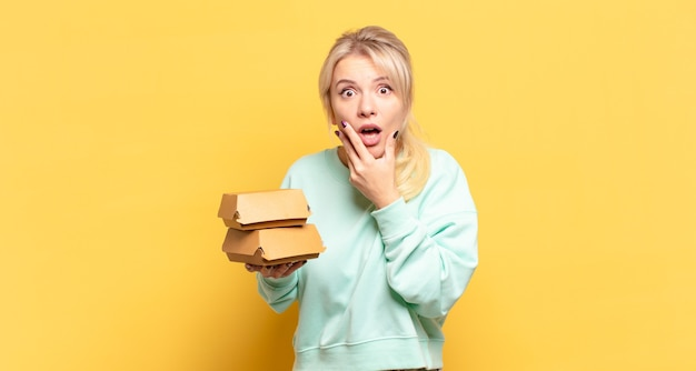 Mulher loira com boca e olhos bem abertos e mão no queixo, sentindo-se desagradavelmente chocada, dizendo o quê ou uau