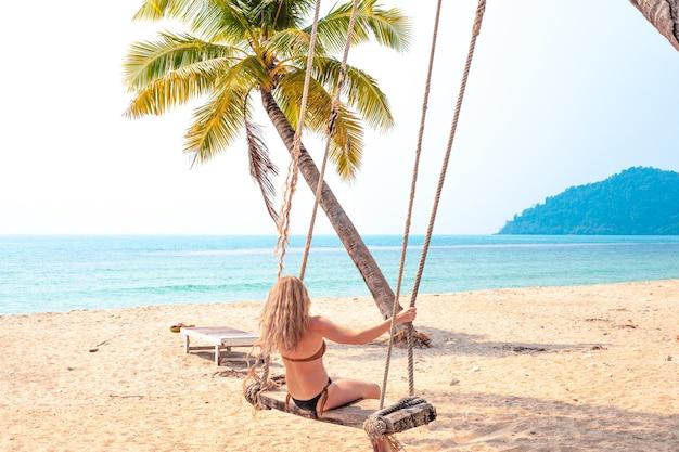 Mulher loira com cabelo comprido balançando em um balanço suspenso em uma palmeira perto do mar na tailândia, retrovisor, pessoas reais.