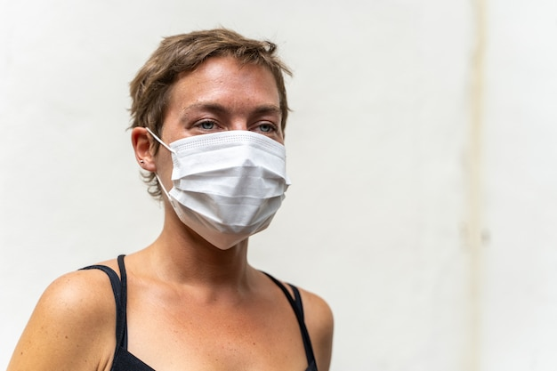 Mulher loira com cabelo curto e uma máscara no rosto para protegê-la de vírus