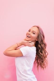 Mulher loira com cabelo lindo encaracolado sorrindo isolada na parede rosa.