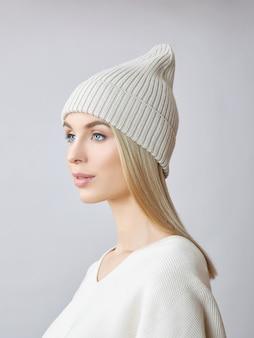 Mulher loira com cabelos longos, vestindo um chapéu e uma camisola branca. retrato da beleza de uma menina.