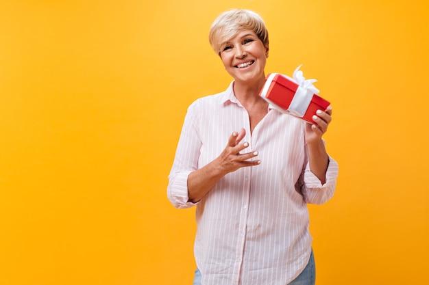 Mulher loira com camisa listrada segurando uma caixa de presente em fundo laranja